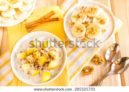 Oatmeal porridge with fruits (banana, apple) and nuts over wooden table, healthy organic breakfast - stock photo