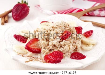 Oatmeal porridge with milk, strawberry, banana and cinnamon - stock photo