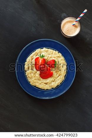 Oatmeal porridge with strawberries in vintage blue plate on a dark surface with chocolate milkshake, top view. Healthy breakfast - stock photo