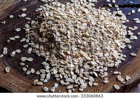 Oatmeal rolled oats grain heap on rough wooden cutting board from side - stock photo