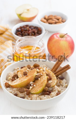 oatmeal with apples, raisins, cinnamon and ingredients on white wooden table, vertical, top view - stock photo