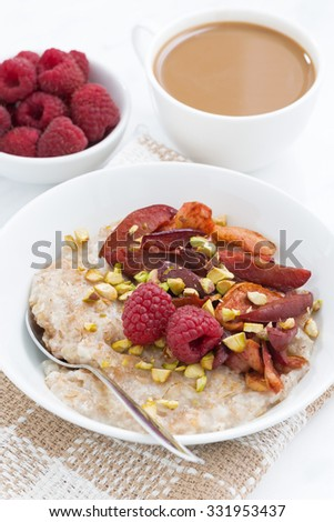 oatmeal with baked fruit, coffee with milk for breakfast, closeup vertical, top view - stock photo