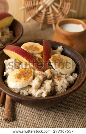 Oatmeal with banana, apple and cinnamon in the bowl, cinnamon sticks and cup of milk on sackcloth - stock photo