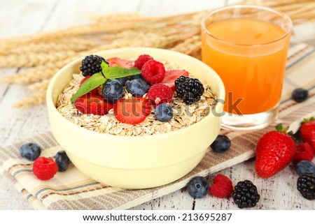 Oatmeal with berries on white wooden background - stock photo