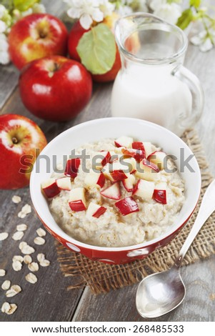Oatmeal with caramelized apples in the orange bowl - stock photo