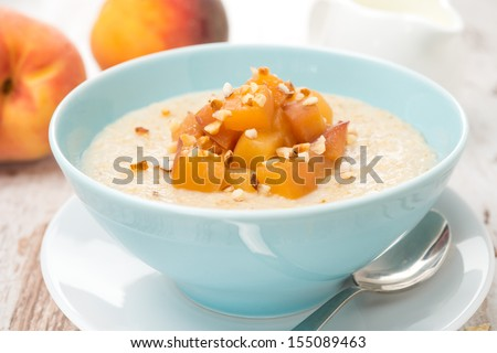 oatmeal with caramelized peaches in a bowl and jug of yogurt for breakfast, close-up, horizontal - stock photo