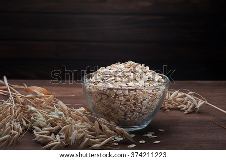 oatmeal with ears of oats and a glass of milk on wooden dark background - stock photo