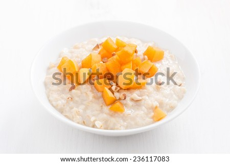 oatmeal with fresh apricots and nuts on a white wooden table, top view, close-up - stock photo