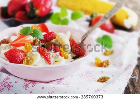 oatmeal with fresh strawberries, banana and raisins on the table. close-up.health or cooking concept. selective focus - stock photo
