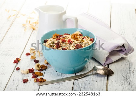 oatmeal with nuts and dried fruits on old white painted wooden table. Perfect breakfast - stock photo