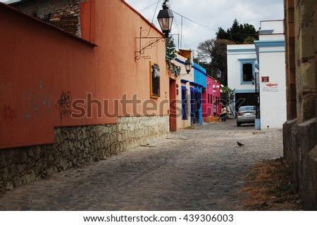 OAXACA, OAXACA, MEXICO- DECEMBER 13, 2013: An empty street with typical mexican houses and bright and vibrant colors in Oaxaca, Mexico - stock photo