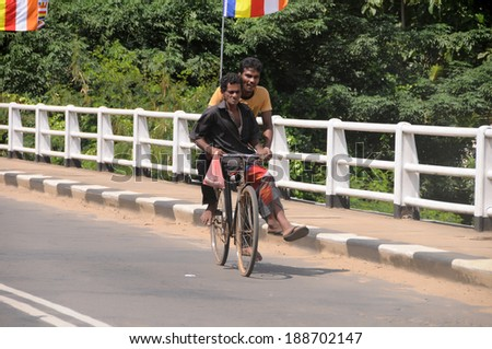 OBBEGODA, SRI LANKA JANUARY 15: Unidentified people biking on the main road on January 15, 2014 in Obbegoda,Sri Lanka.This is a way of transportation for the poor people that can�´t afford a riskaw - stock photo