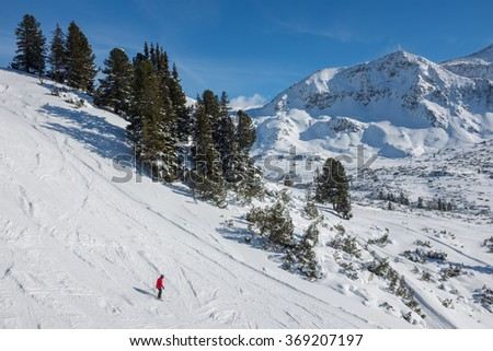 Obertauern, Austria - January 20, 2016: A skier goes down a slope in a ski resort. - stock photo