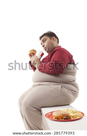 Obese man eating junk food - stock photo