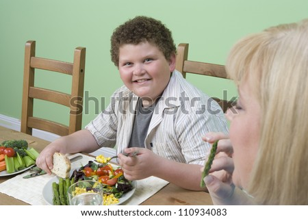 Obese mother and son having meal at home - stock photo