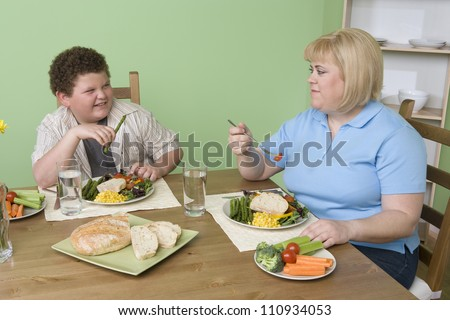 Obese mother and son having meal together at home - stock photo