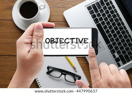 OBJECTIVE                    message on hand holding to touch a phone, top view, table computer coffee and book - stock photo