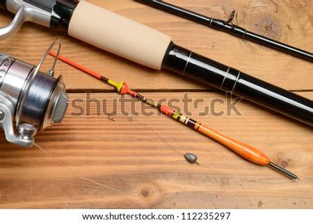 Objects for fishing. The rod with reel, a float, fishing line and hook on a wooden surface - stock photo