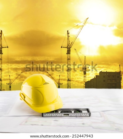 Objects of safety helmet level lie blue print architect paper plan on table with sunset sky with Nature scene building construction crane lift load against evening sun rise shine and new modern house - stock photo
