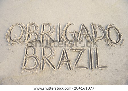 Obrigado Brazil thank you message in Portuguese handwriting in sand - stock photo