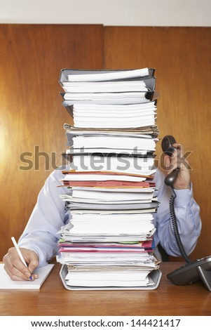 Obscured office worker using telephone while writing document behind a stack of folders at desk - stock photo
