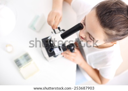 Observation through a microscope, an interesting lesson of nature. The girl observed through a microscope biological preparations - stock photo