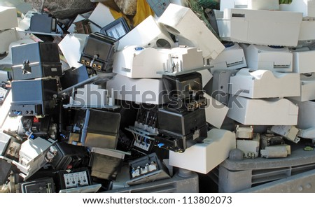 Obsolete counters of electricity thrown in waste landfill - stock photo