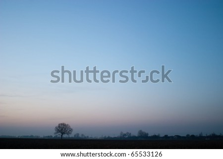 occurring yellow sun behind the clouds on a warm evening - stock photo