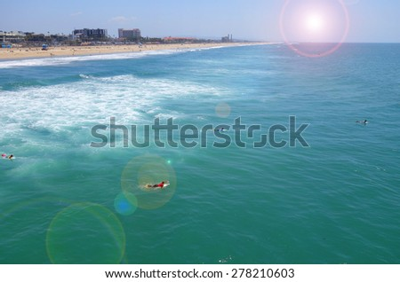 ocean and beach with bright sun flare and people swimming and surfing                               - stock photo