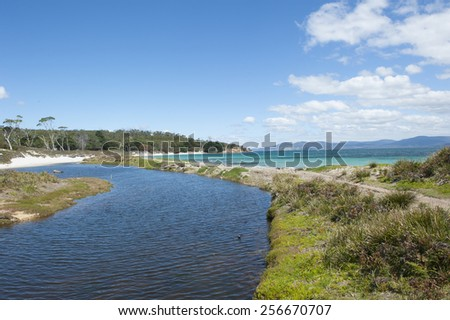 Ocean Beach and river inlet on Maria Island, Tasmania, Australia, World Heritage Site and National Park, with mountains along coastline in blurred background, blue sky, copy space. - stock photo