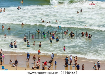 OCEAN CITY - JUNE 14: Beach full of people in Ocean City, MD on June 14, 2014 during OC Airshow. Ocean City, MD is a popular beach resorts on East Coast and one of the cleanest in the country. - stock photo