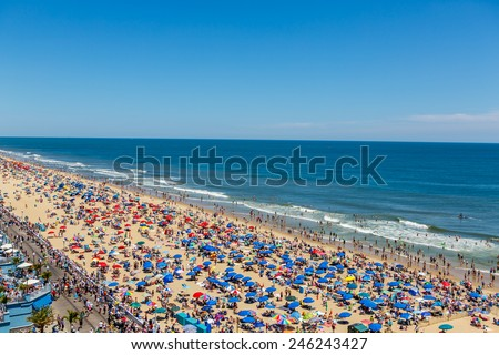 OCEAN CITY - JUNE 14: Crowded beach covered with umbrellas in Ocean City, MD on June 14, 2014. Ocean City, MD is a popular beach resort on the East Coast and one of the cleanest in the country. - stock photo