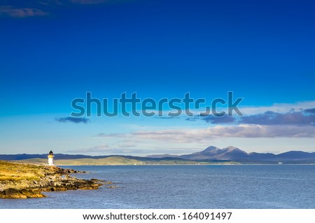 Ocean coast lighthouse in Port Charlotte, Scotland, United Kingdom - stock photo