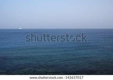 Ocean landscape under blue sky with sailboat. - stock photo