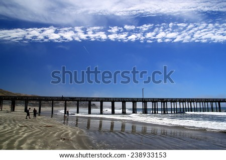 Ocean Pier. A pier goes into the ocean. People are strolling in the distance. A white cloud mirrors the pier in the sky. - stock photo