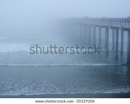 Ocean pier, disapearing in the fog - stock photo