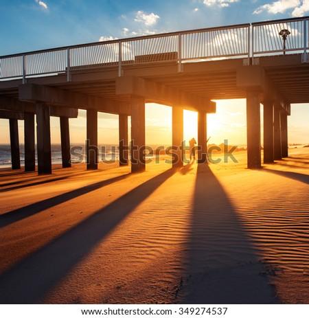 Ocean pier under warm sunset  - stock photo