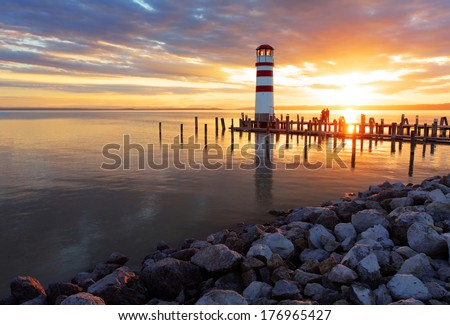 Ocean sunset with lighthouse - stock photo