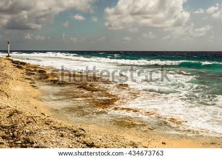 Ocean surf and lighthouse off the coast of the atoll Raiatea, French Polynesia, in sunny weather - stock photo