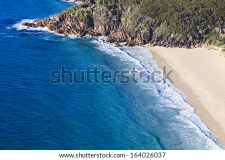 ocean surf waves at empty summer clean sandy beach of a small bay in rocks aerial view - stock photo