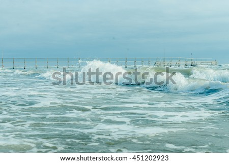Ocean theme: sea shore, turquoise waves, splashes, breaking wave, surf, pier in the background - stock photo