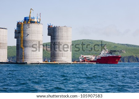 Ocean tug at the base of offshore oil drilling platform. Sea Japan. Russian coast. - stock photo