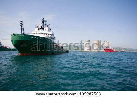 Ocean tugs towing base offshore oil drilling platform. Sea of Japan. Russian coast. - stock photo