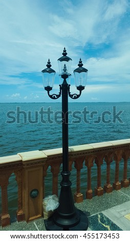 Ocean view from wooden pier with a Three Light Outdoor Lamp Post - stock photo