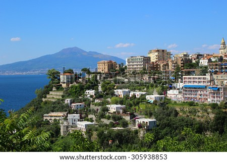 Ocean view of coastal features of Italy in Sorrento with cliffside houses and Mount Vesuvius in the background - stock photo