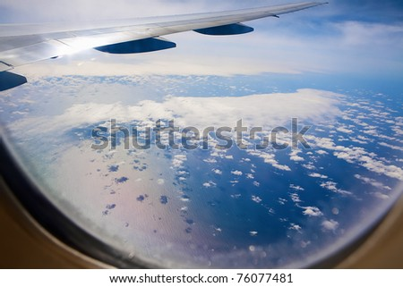 Ocean view through the airplane. Water, clouds, shadows. - stock photo