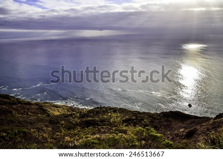 Ocean water in the bay shimmering in the sun light at sunset. - stock photo