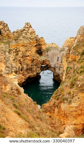 Ocean water seen through hole in rocks. Stone arches, caves, rock formations at Dona Ana Beach (Lagos, Algarve coast, Portugal) in the evening light. - stock photo