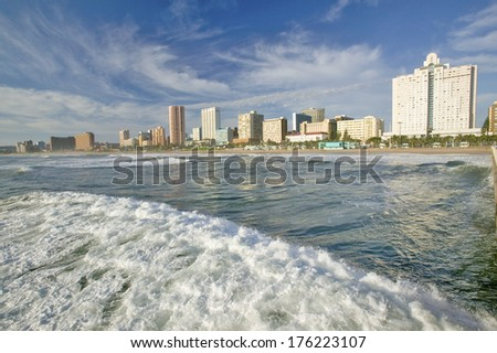 Ocean wave comes in Durban skyline, South Africa on the Indian Ocean - stock photo
