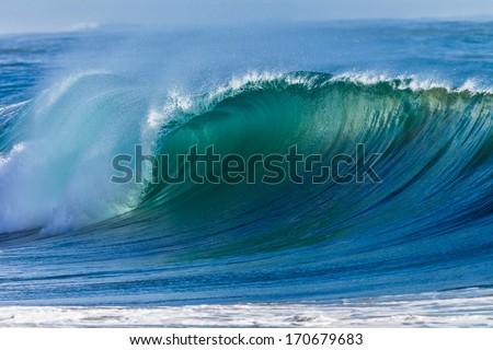 Ocean Wave Curl  Clean ocean wave rolling curling lip crashing on shallow sandbars. - stock photo